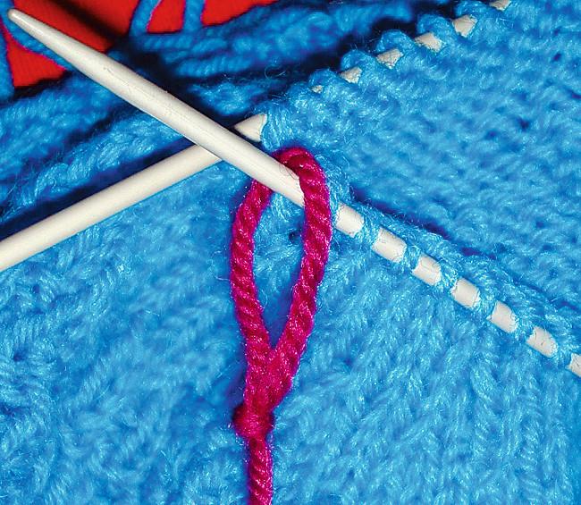 Fotografi av et strikketøy med en merketråd festet mellom to masker.