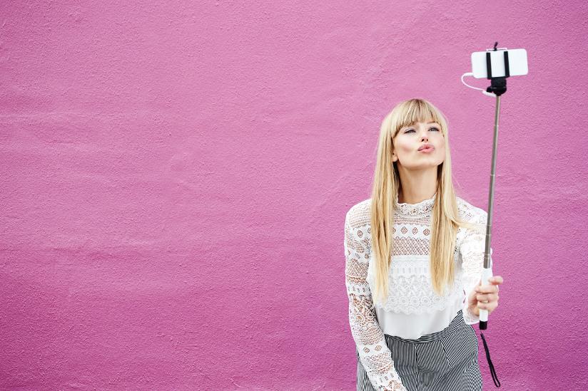 Fotografi av en ung kvinne som poserer mens hun tar en selfie med selfiestang.