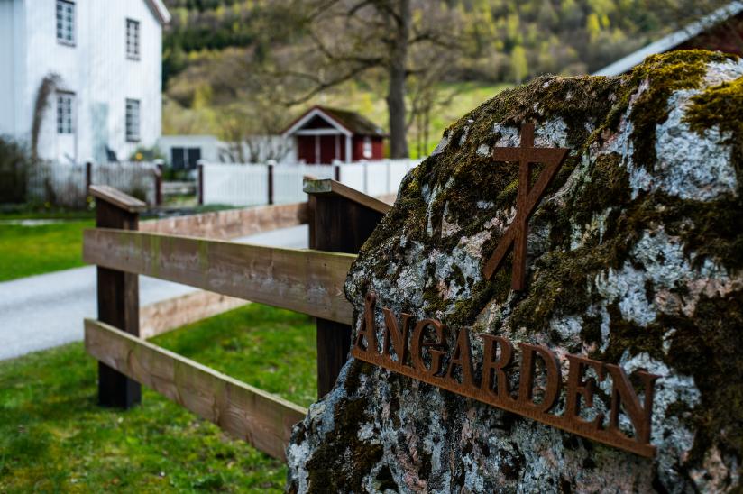 Fotografi med nærbilde av et bumerke som er plassert på en stein. Bumerket følger gården som skimtes i bakgrunn.