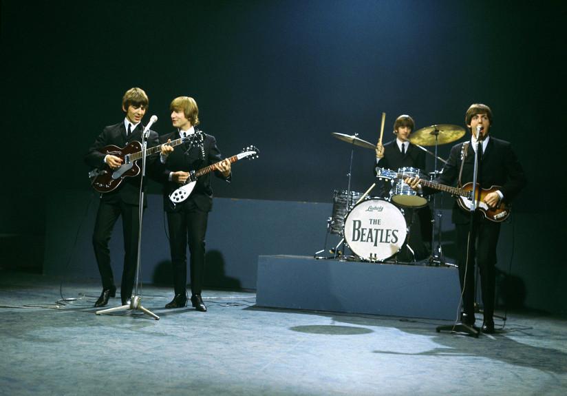 Fotografi av The Beatles – George Harrison (vokal og gitar), John Lennon (vokal og girar), Ringo Starr (trommer) og Paul McCartney (vokal og gitar) – som opptrer på en scene.