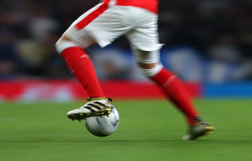 Fotografi av en fotballspiller som dribler med en ball.