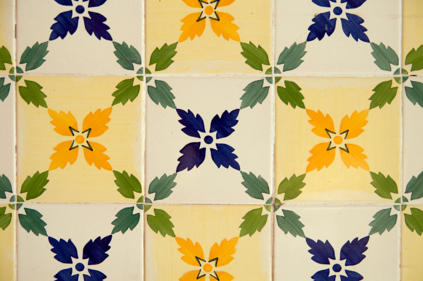 Fotografi med nærbilde av keramiske fliser hvor blomsterblader i blått, grønt og gult danner et mønster med diagonale linjer.