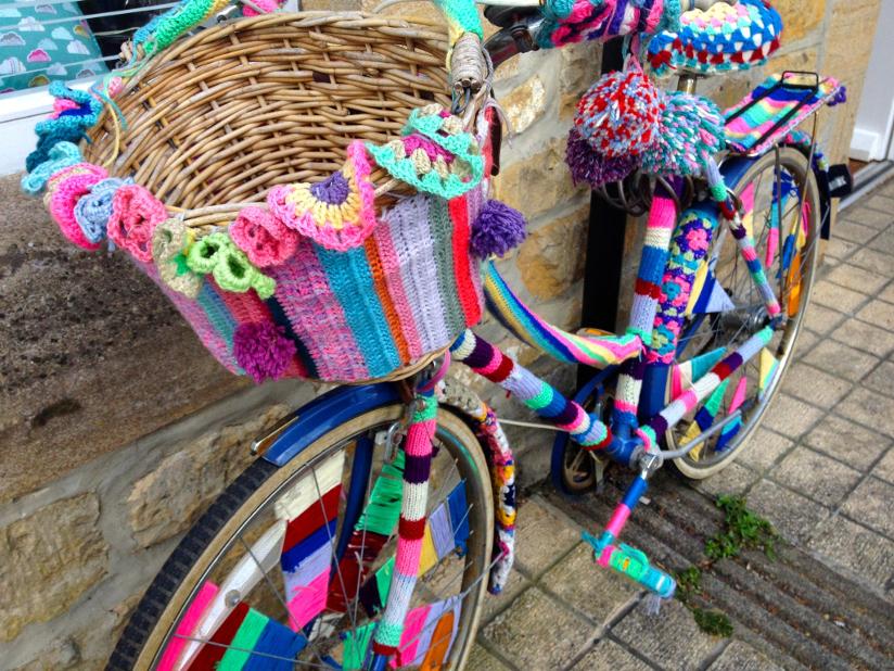 Fotografi av en parkert sykkel med kurv som er dekket med fargerike strikketøy med mange farger (yarnbombing/geriljastrikking). Strikketøyet har et stripete mønster. Kurven er dekorert med blomster og garndusker.