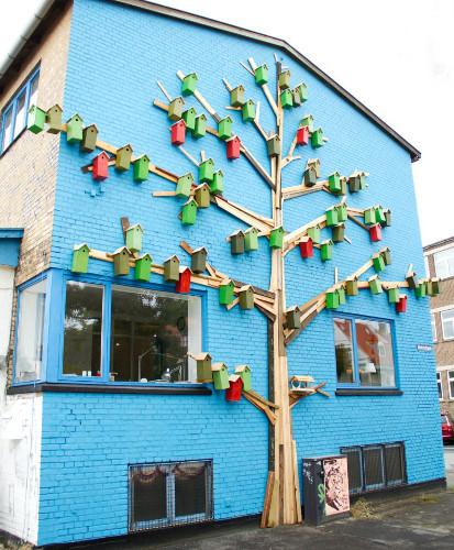 Fotografi av en blåmalt yttervegg på en boligblokk. Kunstneren har montert et tre som er laget av planker på veggen. På grenen henger det mange fuglekasser i forskjellige farger.