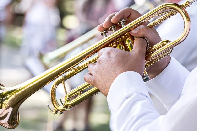 Fotografi med nærbilde av en mann som spiller på en trompet med ventiler.