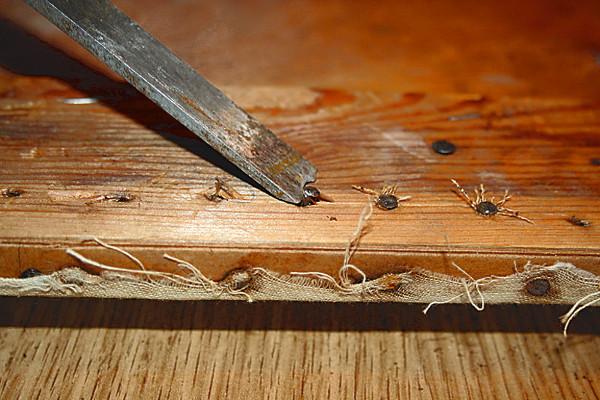 Fotografi som viser hvordan spiker fjernes fra seteplate av tre.