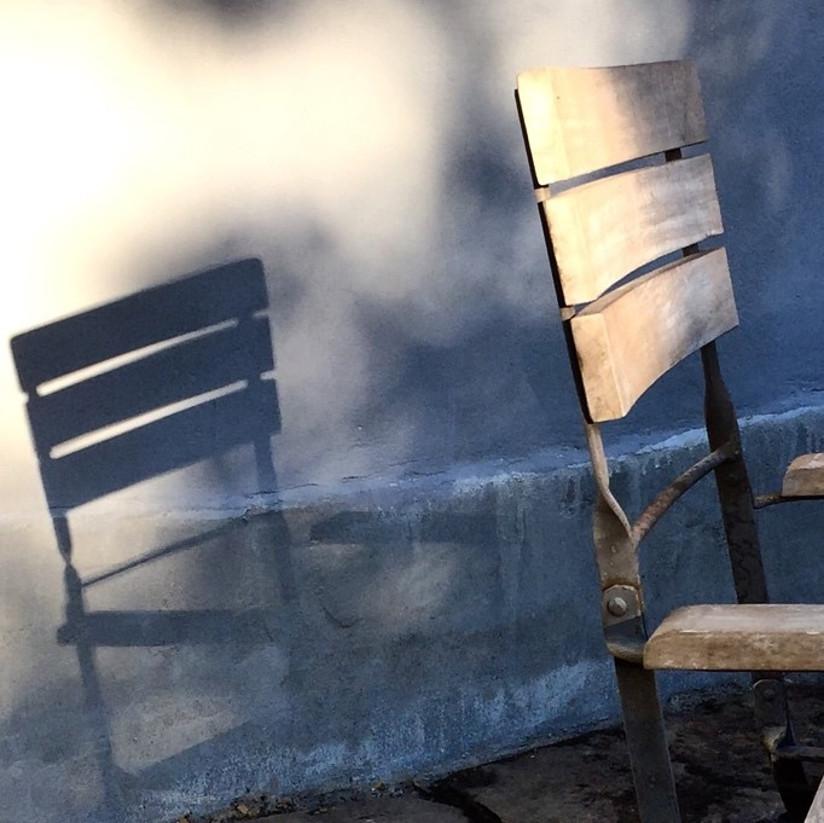 Fotografi av en tom stol som avgir skygge på vegg.