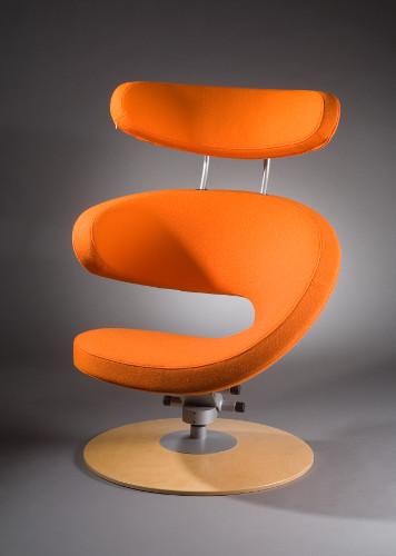 Fotografi av lenestolen Peel som er designet av Olav Eldøy. Stolen er oransje og ser ut som et appelinskall som er skrellet av i en remse.