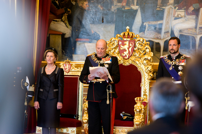 Fotografi av kong Harald som leser trontalen foran den forgylte tronstolen i Stortinget. Dronning Sonja står til venstre for kongen. Kronprins Haakon står til høyre for kongen. Kongen og kronprinsen har på seg uniformer med ordensbånd og medaljer.