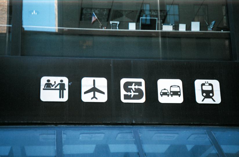 Fotografi av skilt med informasjonsgrafikk ved et trafikalt knutepunkt i New York. Informasjonsgrafikken, de visuelle ordbildene, beskriver blant annet en billettskranke, et fly, en drosje, en buss og et tog.