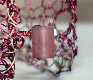 Fotografi av et armbånd med nærbilde av lås som er laget av en perle. Armbåndet er strikket med tynn metalltråd og perler.