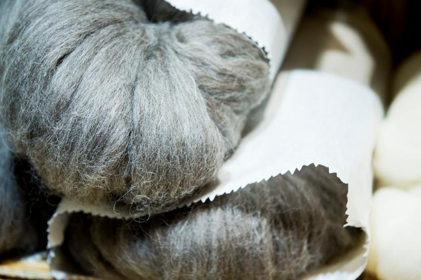Fotografi av to grå garnnøster som delvis er dekket av papir.