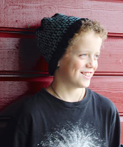 Fotografi av en ung gutt som har på seg lue. Luen er strikket etter mønster med to forskjellige farger.