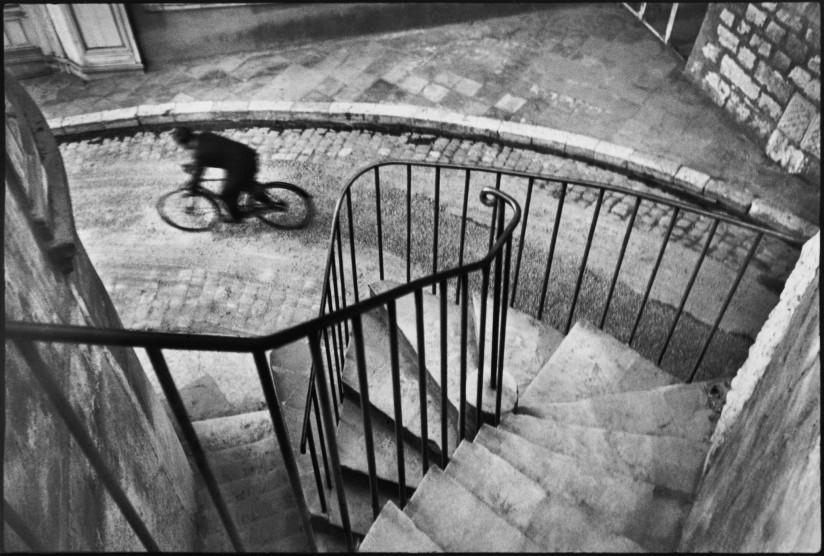 Svart-hvitt fotografi tatt på toppen av en trapp i et urbant miljø. En mann sykler på gateplan. Syklisten er i bevegelse og framstår som utydelig.