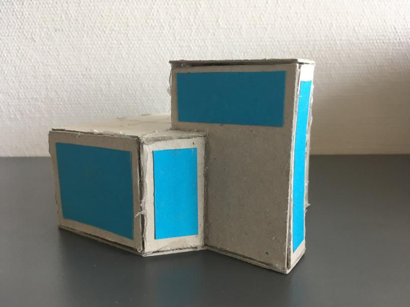 Fotografi av en modell av en hytte laget i papp.