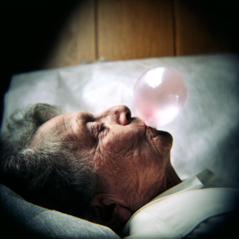 Fotografi av en eldre dame som hviler hodet på en pute mens hun blåser en rosa tyggegummiboble.