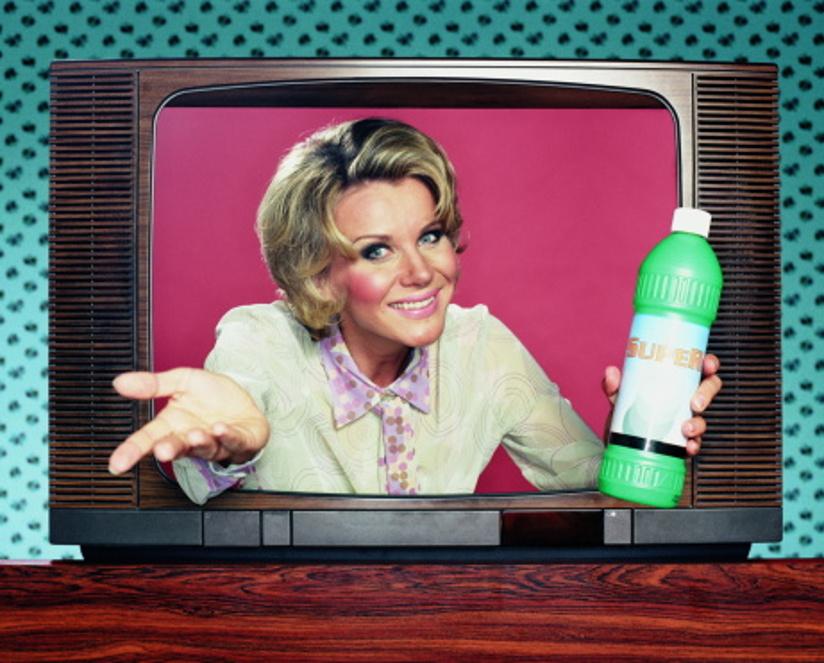 Reklameannonse for et vaskemiddel. I utgangspunktet er en kvinne fotografert innenfor rammen av en TV-skerm, men armene og produktet hun holder i venstre hånd kommer ut av TV-rammen.
