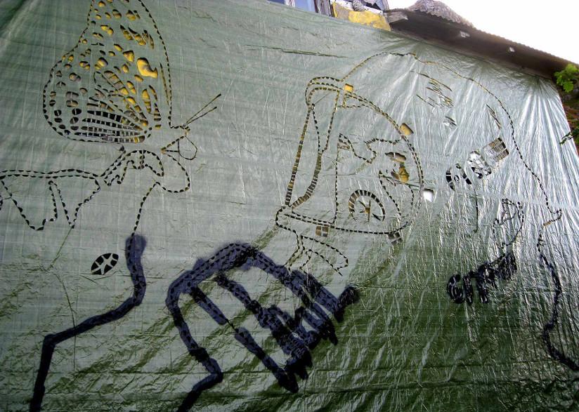 Fotografi av en husvegg som er dekket av en presenning med skisser av graffiti. Motivet er nærbilde av en person med gassmaske som ser på en finger der en sommerfugl har landet.