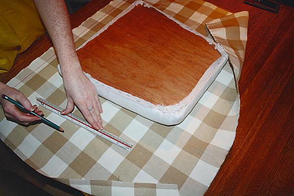 Fotografi av seteplate som ligger på stoff som skal bli setetrekk. En jente måler størrelsen på soffet slik at det senere kan brettes inn og festes under seteplaten.
