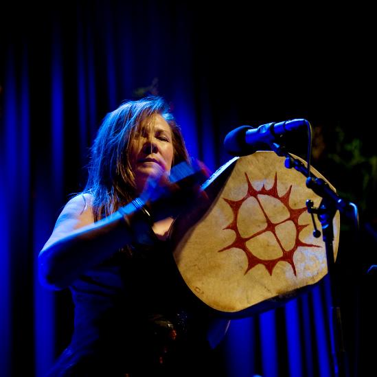 Fotografi av Mari Boine – sanger og musiker – som spiller på en samisk tromme.