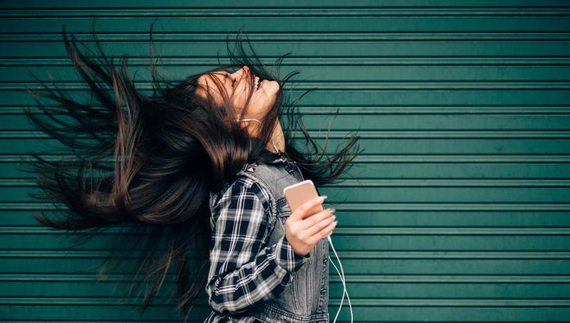 Fotografi av en jente som lytter og danser til musikk hun lytter til via smarttelefon.