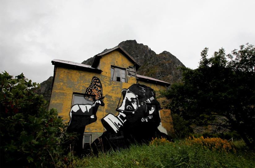 Fotografi av en husvegg med graffiti på veggen. Motivet er nærbilde av en person med gassmaske som ser på en finger der en sommerfugl har landet.