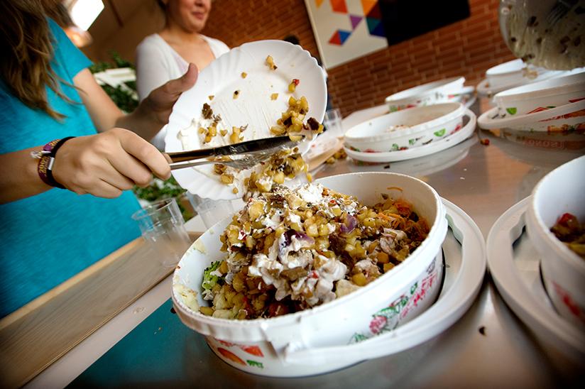 Fotografi av mennesker som samler sammen matrester etter et måltid.