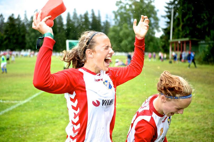 Fotografi av to jenter som nettopp har spilt fotballkamp. Draktene de har på seg viser logoene til bedriftene som sponser fotballaget.