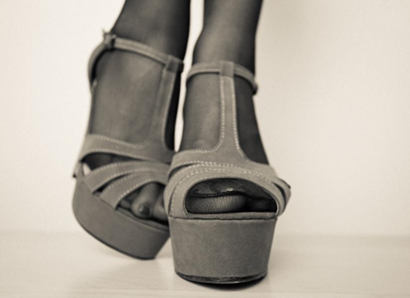 Svart-hvitt fotografi med nærbilde av føtter ikledd nylonstrømper i platåsandaler.