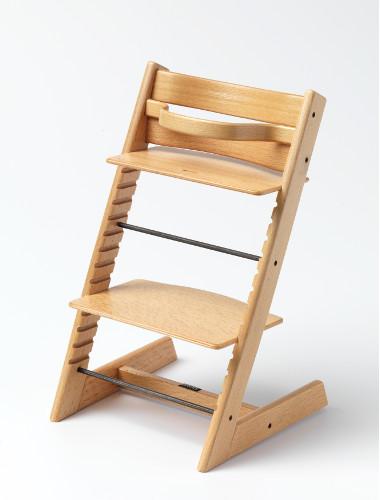 Fotografi av Tripp Trapp Barnestol av tre som er designet av Peter Opsvik. Seteplate og fotbrett kan justeres ettersom barnet vokser.