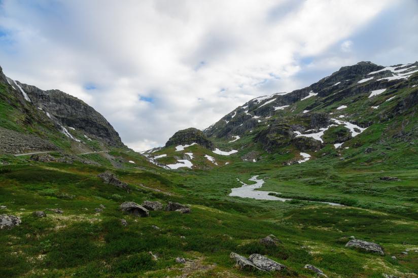 Fotografi av et dalføre i fjellandskap med grønt gress og noen flekker med snø.