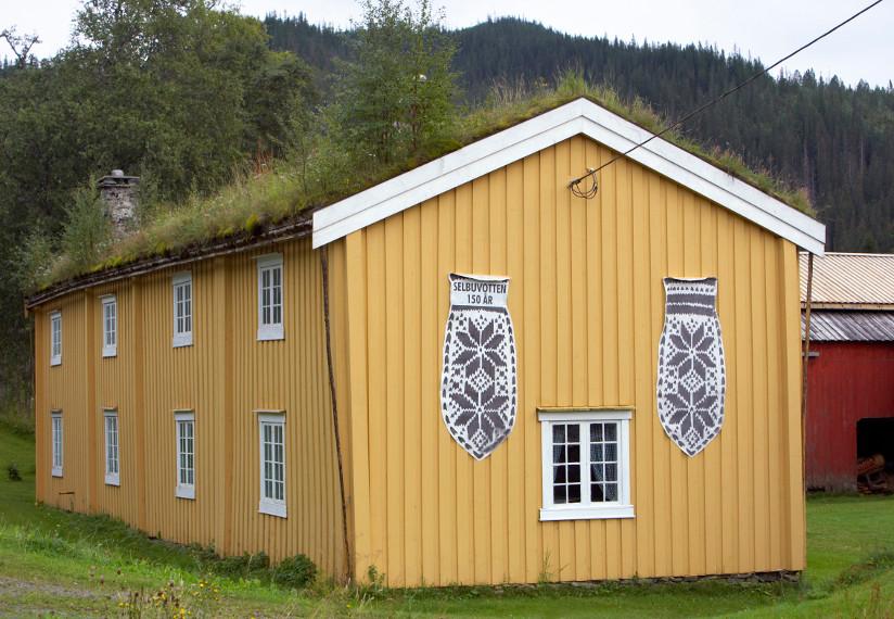 Fotografi av et gult gårdshus med torvtak. To store Selbuvotter henger på en endevegg.
