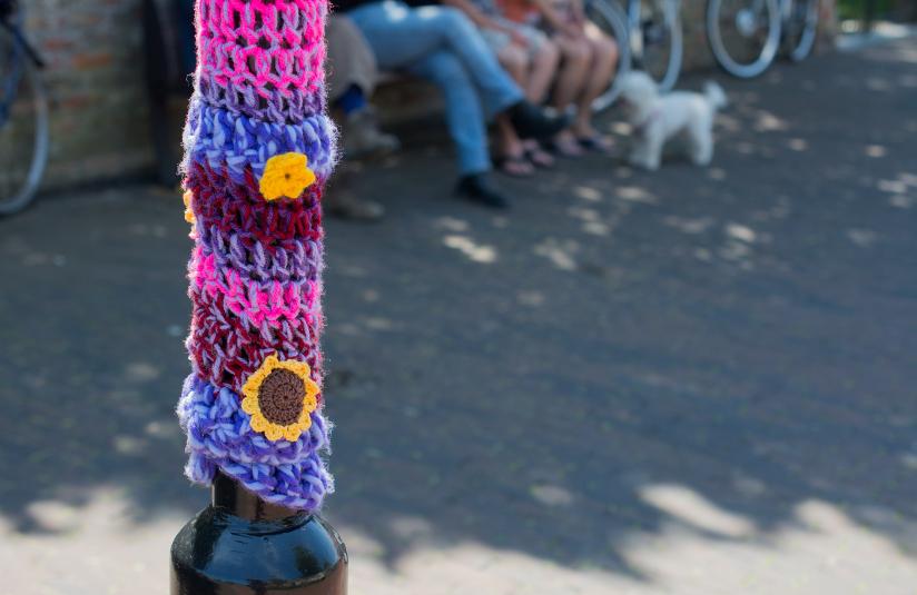 Fotografi av en lyktestolpe i et urbant miljø som er dekket av garn i forskjellige farger (yarnbombing/geriljastrikking). Strikketøyet har et stripete mønster basert på brede masker og er dekortert med to blomster – en gul blomst samt en solskikke.