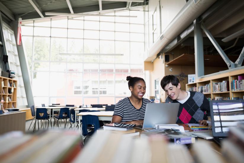Fotografi av to elever som jobber sammen i et bibliotek.
