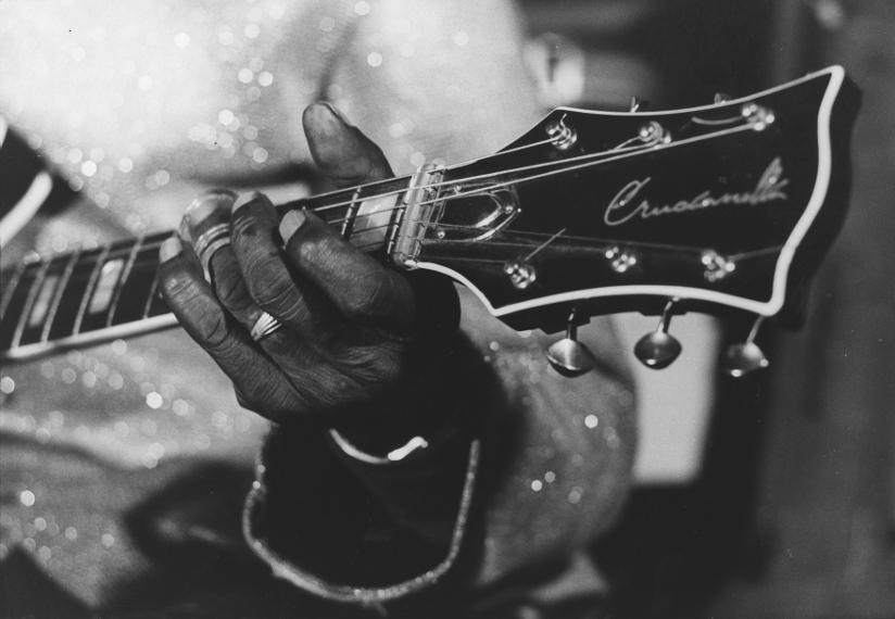 Svart-hvitt fotografi med nærbilde av en gitar og hånden til Fred McDowell (1904–1972) som tar et gitargrep.