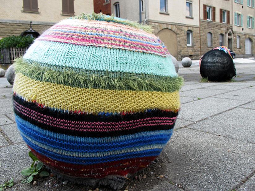 Fotografi av en betongball i et urbant miljø som er dekket av garn i forskjellige farger. (yarnbombing/geriljastrikking). Strikketøyet har stor masker og et stripete mønster. I bakgrunnen skimter vi en tilsvarende ball som er dekket av et stort strikketøy strikket med større masker.