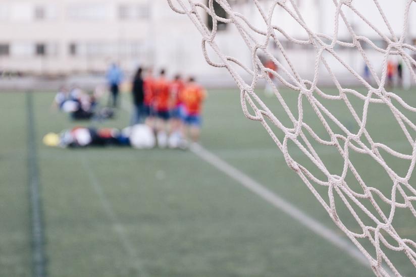 Fotografi med nærblide av nettingen i et fotballmål. I bakgrunnen ser vi fotballspillere som står på sidelinjen.