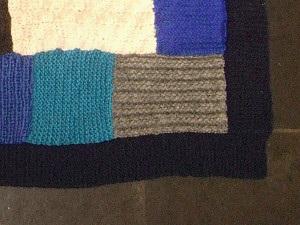 Fotografi som viser detaljer fra ferdig lappeteppe. Nærbilde av ruter med forskjellige mønstre og farger samt ytre ramme.
