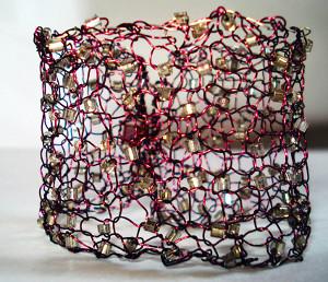Fotografi av et armbånd som er strikket med tynn metalltråd og perler.