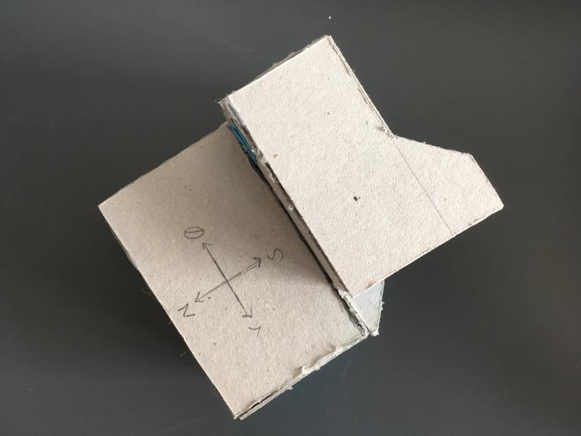Fotografi av en modell av en hytte i papp sett ovenfra.