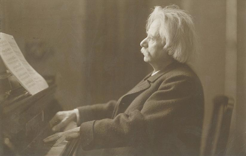 Svart-hvitt fotografi av Edvard Grieg som spiller på et flygel, ca 1900.