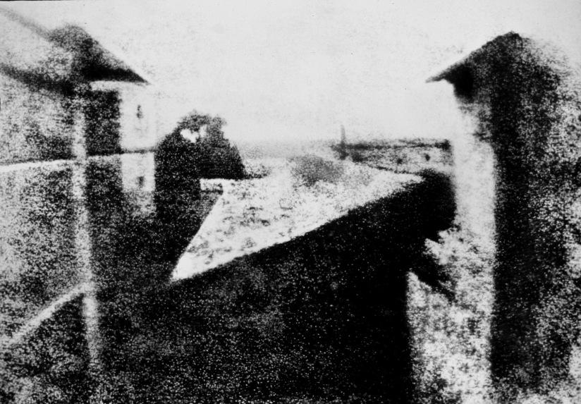Svart-hvitt fotografi av en bakgård. Fotografiet er uskarpt og kornete etter lang eksponeringstid (8 timer), og er det første som ble tatt med et hullkamera.