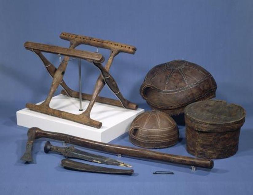 Fotografi av gjenstander (en klappstol i tre, en øks med langt skaft, en dolk osv.) funnet i en vikinggrav.