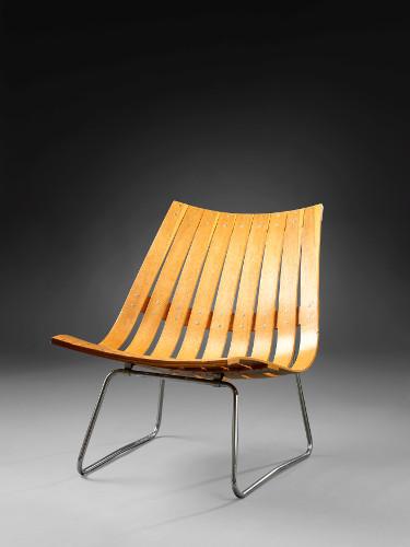 Fotografi av en lenestol laget av formbøyd tre og stålrør. Stolen er modernistisk og designet av Kjell Richardsen.