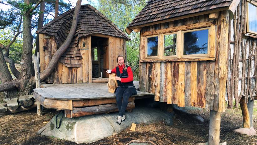 Fotografi av en kvinne som sitter på trammen utenfor en rustikk hytte. Hun holder en kopp i hånden og smiler mot fotografen.
