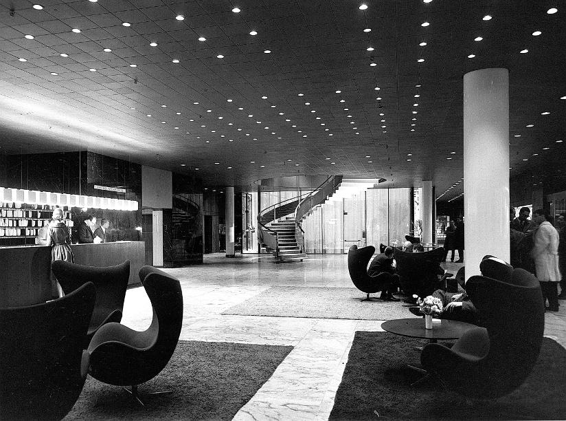 Svart-hvitt fotografi fra lobbyen i SAS Royal Hotel på 1960-tallet. Lobbyen er møblert med Egget-stoler designet av Arne Jacobsen.