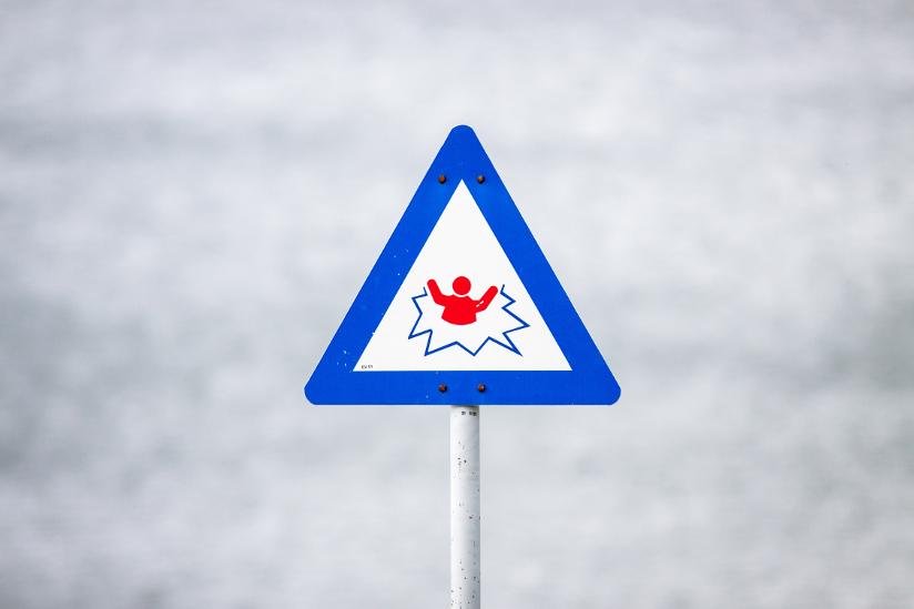 Fotografi med nærbilde av et skilt som varsler om usikker is med informasjonsgrafikk.