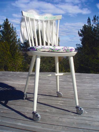 Fotografi av en trestol som er malt hvit. Stolen har en mønstret sittepute og hjul på fire ben.