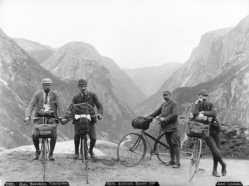 Svart-hvitt fotografi av fire menn på sykkeltur i Sogn og Fjordane i 1880-årene.