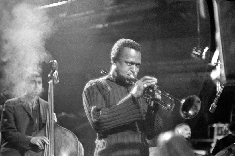 Svart-hvitt fotografi av Miles Davis (1926–1991) som spiller på en trompet i New York i 1959. Bak Davis ser vi en musiker som spiller på kontrabass samt en pianist.